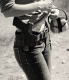 Woman with gun. Woman wearing jeans, with gun and earphones. Black and white Royalty Free Stock Images