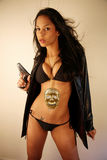 Woman with a gun. Woman wearing a bikini, leather jacket and golden skull medallion with a gun in her hand Royalty Free Stock Photography