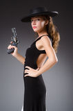 Woman with gun against stock photo