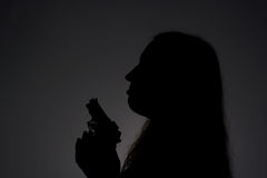 Woman with gun in darkness Stock Photos