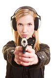 Woman with gun and ear protection. Young female shooter with pistol and ear protection Stock Image