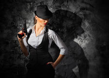 Woman with gun. On grey wall background Stock Image