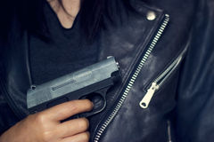 Woman with gun in hand on the black jacket texture background Stock Image