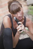 Woman with gun hiding Stock Images