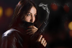 Woman with gun. Woman in leather coat with smoking gun Royalty Free Stock Image