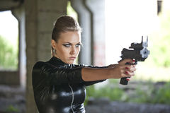 Woman with gun in leather suit Royalty Free Stock Image