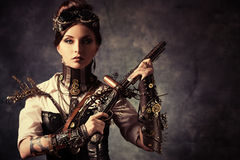 Woman gun. Portrait of a beautiful steampunk woman holding a gun over grunge background