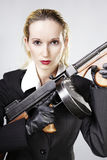 Woman with gun in studio portrait. Mafia style fashion studio portrait - nice young woman posing with Tommy gun for figure and portrait photos in retro criminal royalty free stock image