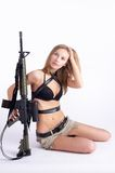 Woman with gun on white. Beautiful sexy blond woman holding army rifle Stock Photo