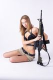 Woman with gun on white. Beautiful sexy blond woman holding army rifle Stock Photos