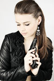 Woman with a gun. Young beautiful woman in a black jacket with a gun royalty free stock images