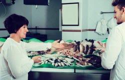 Woman  and guy selecting fish Stock Image