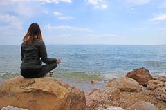 Woman in gyan mudra on the rocks Royalty Free Stock Photos