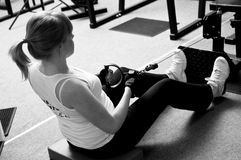 Woman in gym. Black and white image of a woman working out in a gym, sitting on the floor and pulling weights Royalty Free Stock Photo