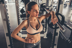 Woman at the gym. Attractive girl is working out with barbell in gym Royalty Free Stock Photos