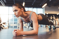 Woman at the gym. Attractive young woman is doing plank exercise while working out in gym Stock Photography