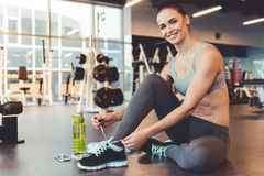 Woman at the gym. Attractive young woman is lacing up her training shoes, looking at camera and smiling while working out in gym Royalty Free Stock Image