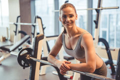 Woman at the gym. Attractive young woman is leaning on the barbell, looking at camera and smiling while working out in gym Royalty Free Stock Images