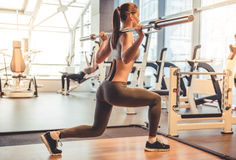 Woman at the gym. Attractive young woman is lifting weight while working out with barbell in gym Stock Photo