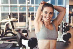 Woman at the gym. Attractive young woman is looking at camera and smiling while stretching hands in gym stock image
