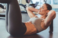 Woman at the gym. Attractive young woman is smiling while doing abs in gym Royalty Free Stock Photography
