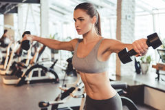 Woman at the gym. Attractive young woman is working out with dumbbells in gym Royalty Free Stock Photography
