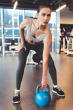 Woman at the gym. Attractive young woman is working out with kettlebell in gym Stock Photo