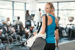 Woman with gym bag. Fit woman holding gym bag in a fitness centre. Beautiful blonde woman ready to start her training. Portrait of energetic woman looking at stock photo