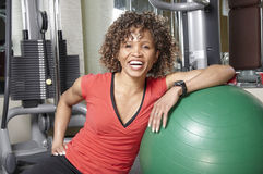 Woman with gym ball. Smiling African American woman resting against a fitness ball in the gym Stock Photos