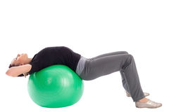 Woman with Gym Ball Doing Situps Exercise. Young woman with gym ball doing situps exercise, isolated on white background Royalty Free Stock Images