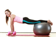 Woman with gym ball and dumb bells isolated Royalty Free Stock Image