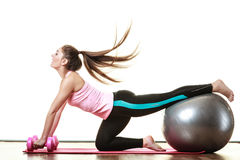 Woman with gym ball and dumb bells isolated Stock Photography
