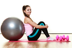 Woman with gym ball and dumb bells isolated Royalty Free Stock Images