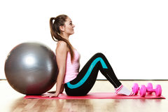 Woman with gym ball and dumb bells isolated Stock Image