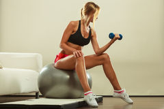Woman with gym ball and dumbbell doing exercise Royalty Free Stock Photography
