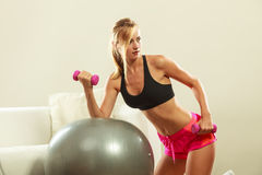Woman with gym ball and dumbbell doing exercise Royalty Free Stock Photo