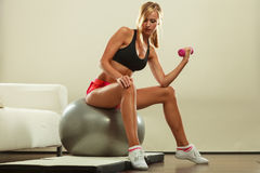Woman with gym ball and dumbbell doing exercise Royalty Free Stock Images