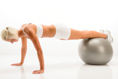Woman gym ball pushups at white fitness Royalty Free Stock Images