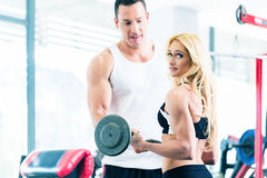 Woman in gym with barbell assisted by fitness trainer Stock Image
