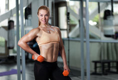 Woman in the gym with barbell Stock Photography