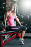 Woman at the gym on a bench. Fit young woman working out in the gym Stock Photo