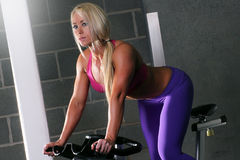Woman at the gym on a bike. Attractive fitness woman with a toned body working out on an exercise bike at the gym Royalty Free Stock Images