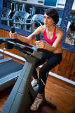 Woman in gym on bycicle. Woman in gym working on bycicle machine Royalty Free Stock Images