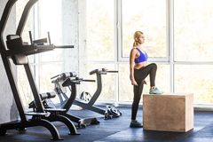 Woman in gym doing cross fit exercise step up on box. stock photography