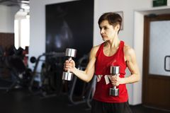 Woman in the gym doing exercises with dumbbells stock photography