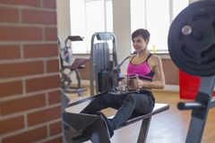 Woman in gym doing strength training on the simulator. The woman in gym doing strength training on the simulator Stock Photo