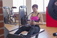 Woman in gym doing strength training on the simulator. The woman in gym doing strength training on the simulator Royalty Free Stock Photos