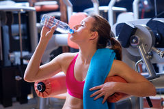 Woman in gym drinks water Royalty Free Stock Image