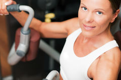 Woman in gym exercising. Woman doing fitness training on a butterfly machine with weights in a gym Royalty Free Stock Photo