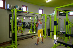 Woman at the gym exercising. A woman strengthens front of a mirror Royalty Free Stock Images